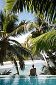 Woman sitting on edge of infinity pool overlooking coastline, North Island, Seychelles