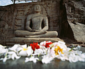 Seated Buddha and flower offerings, Polonnaruwa, North Central Province, Sri Lanka