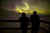 Two tourists watching Aurora Borealis from Aurora Sky Station, Abisko, Sweden