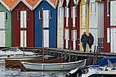A couple strolling past the colourful fishing huts along the quayside at Smogen, Sotenas Municipality, Sweden.