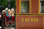 Children look on at the narrow-gauged railway at Mariefred, Sweden