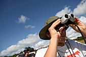 Young man looking through binoculars, Tanzania