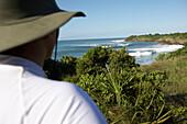 Tourist in hat looking over lush coastline, Tanzania
