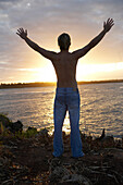 Traveler with arms raised to setting sun, Tanzania