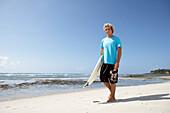 Blond surfer walking on beach with surfboard, Tanzania