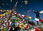 Pilgrim throwing prayer flags, Bompori Hill, Lhasa, Tibet