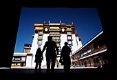 Silhouette of pilgrims going through entrance to visit the Potala Palace, Lhasa, Tibet