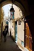 Man walking down a back alley in medina, Tunis, Tunisia