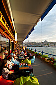 Bars and along the bottom of Galata Bridge at night with the New Mosque behind, Istanbul Turkey