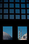 Looking out window and across the domed rooves of the Haghia Sophia to the Sultanahmet or Blue Mosque, Istanbul, Turkey.
