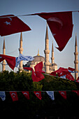 Turkish flags flap in the breeze at dusk over Blue Mosque, Sultanahmet, Istanbul, Turkey