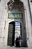 Women in headscarves entering doorway at Blue Mosque, Istanbul, Turkey