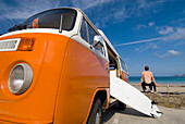 Surfer and board beside orange and white old campervan parked beside the sea, Sennen Cove, Cornwall, England