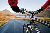 Mountain biker on road in Wasdale, Lake District, England.