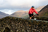 Mountain biker on stone bridge in Wasdale, Lake District, England.