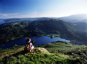 Walker resting above Rydal Water, Lake District, Cumbria, England