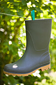Rubber boot suspended in a thread in garden