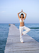 Woman in yoga pose on pontoon