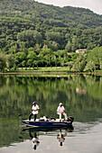 Italy, Veneto, near Vittorio Veneto, fishermen on a lake