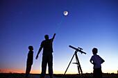 Man showing moon to 2 little boys, telescope