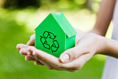 Young woman holding green model house with recycling sign