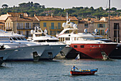 France, Var, Riviera, Saint-Tropez Harbour. Fisherman boat in front, luxurious yachts at rear