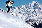 France, Alps, Savoie, Courchevel 1850, female skier in action, Mont Blanc in background