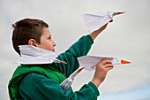 Boy playing with paper airplanes at seaside
