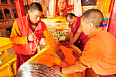 Monks and nun fixing roll with prayers for prayer wheel, nunnery of Lingshed, Lingshed, Zanskar Range Traverse, Zanskar Range, Zanskar, Ladakh, India