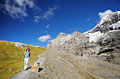 Woman descending, Eiger and Moench in background, UNESCO World Heritage Site Jungfrau-Aletsch protected area, Bernese Oberland, canton of Bern, Switzerland