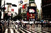 Pedestrians Crossing Busy Intersection in Rain, Tokyo, Japan