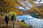 Two female hikers walking along the lakeshore, Feldsee, Feldberg, Black Forest, Baden-Wurttemberg, Germany