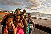 Beach impression with young coloured teenagers at Bloubergstrand, Cape Town, Western Cape, South Africa, RSA, Africa