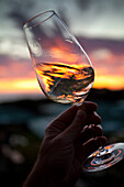 Hand holding and swirling glass of white wine against sunset, Stellenbosch, Western Cape, South Africa
