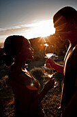 Man und woman enjoying a glass of white wine at sun-set, Stellenbosch, Western Cape, South Africa