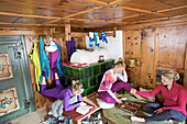 Three young women relaxing after skiing in a cosy alpine hut, See, Tyrol, Austria