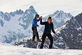 A woman helping a boy across a slackline, Sewenhut, Swiss alps, Kanton Uri, Switzerland