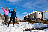 A woman helping a girl balance on a slackline at the Sewenhut, SAC Swiss Alpine-Club, Swiss Alps, Kanton Uri, Switzerland