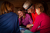 A grandmother reading a bedtime story to a boy and two girls inside a mountain hut, Switzerland