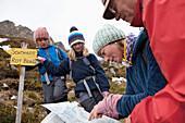 Children and parents study a hiking map, Alps, Kanton Uri, Switzerland