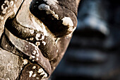 Detail of some of the  216 giant faces of Avalokiteshvara, Giant stone faces watch over visitors in the temple of Bayon. Temples of Angkor, Siem Reap, Cambodia.