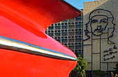 A detail of a classic 50's American car in front of  the imposing image of Che Guevara on the facade of the Ministry of the Interior building in the Plaza de la Revolucion, Havana, Cuba.