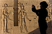 Silhouette of tourist taking photographs in front of large reliefs on walls of Second Pylon, Temple of Isis, Philae Island, near Aswan, Egypt