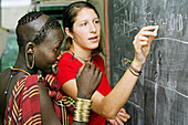 Mursi tribal girl with ear lobes and lower lip pierced during English lesson ran by Christian missionaries, Makki Village, South Omo, Ethiopia
