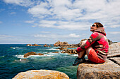 Young woman sitting looking out to sea on rocky shoreline in Brittany, Brittany, France.