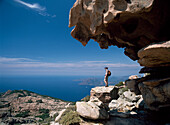 Woman hiker admiring view from beneath Les Calanche rock formations, Corsica, Capo d'Orto near  Porto, Corsica, France