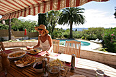 Woman in sunhat eating at table by pool, French Riviera
