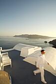 Man in white walking on roof terrace, Katikies, Santorini