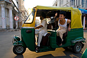 Sikh driving rickshaw with tourist leaning out the back, Delhi, India