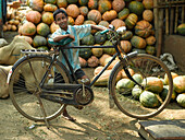 Boy leaning against bicycle infront of pumpkins, Cochin, Kerala, India